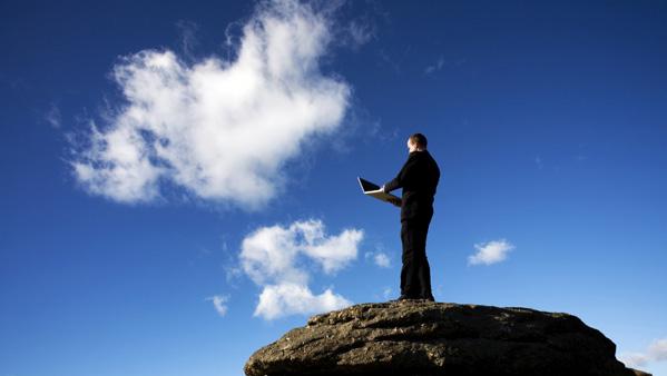 Man on rocks holding laptop up
